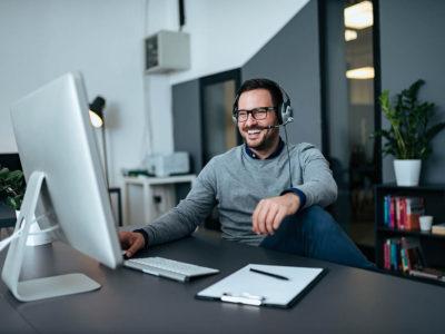 Handsome casual businessman talking online via headset.